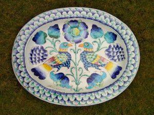 Immagine a colori su piatto di ceramica che rappresenta una natura floreale e animale ideale..... e priva di rischi